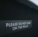 Anti wall-leaning sign on the walls of the concert space inside the Pink Floyd exhibition.